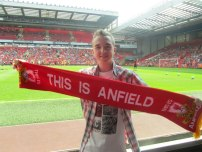 I hold up a 'This is Anfield' scarf at pitchside