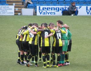 The Burton players huddle up before kick off