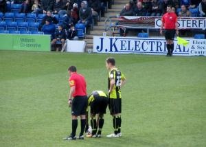 The referee awards Burton a free kick