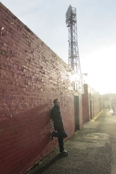 Leaning against the wall of the West Stand
