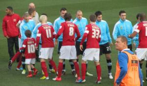 The opposition players shake hands before the game