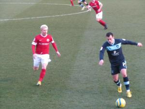 David Perkins and Ross Wallace battle for possession