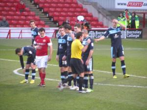 The referee sorts the wall out, before the free kick comes to nothing