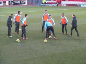 The Burnley substitutes warm up during the break