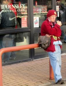 A Burnley fan smokes his pipe outside the stadium