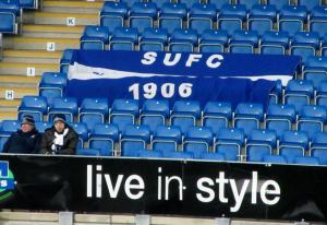 A couple of travelling supporters sit by a flag