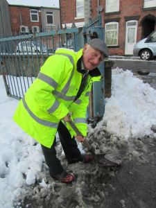 Chesterfield supporter Jeff Hall helps to clear the snow in the car park