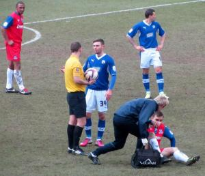 Jay O'Shea has a word with the referee as a Gillingham player receives treatment