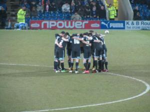 Aldershot huddle up before the game gets underway