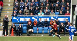 Paul Cook and the home dugout watch the early action