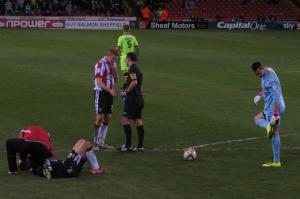 McFadzean receives treatment while Dave Kitson has a word with the referee