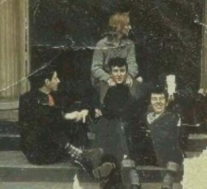 John Lennon and Cynthia sit on the steps with some friends