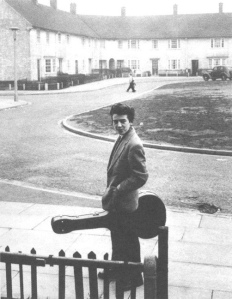 George Harrison with his guitar case outside the house