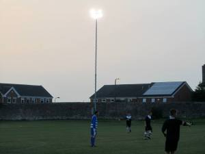 The floodlights shine over the ground