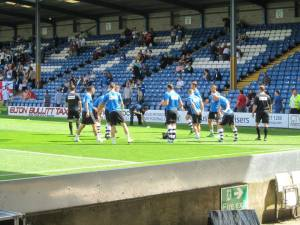 The visiting players warm up ahead of the first game of the new season