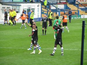 The players applaud and Roberts waves to the fans