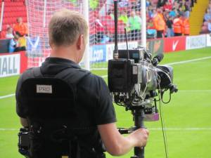 A cameraman on the touchline