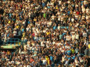 Home fans sit in the evening sunshine