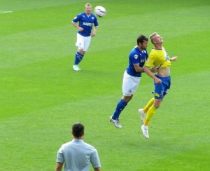 Michael Smith beats Sam Hird to a header