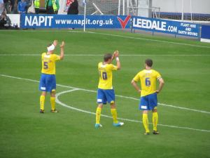 The Dons players applaud their supporters