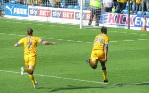 The Mansfield forward runs the length of the pitch to celebrate with the away fans