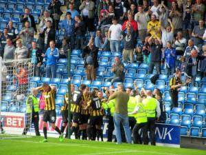 The players and fans celebrate the goal