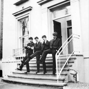 A publicity photo of The Beatles on the steps in 1962