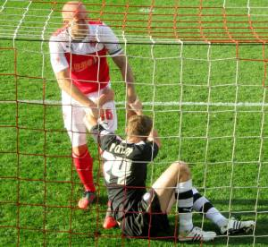 Chris Porter is helped to his feet by Ryan Cresswell after failing to get on the end of a cross