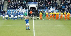 The teams line up on the field