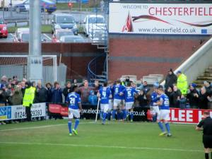 The players celebrate with the supporters following the third goal