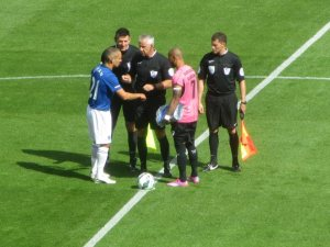 The officials and the two captains exchange handshakes