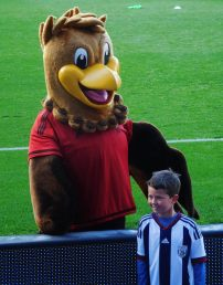 A young Baggies fan has a photo with the mascot